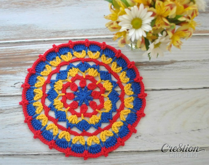 This fun mandala combines treble stitches with simple chains and single crochets to create this pretty design. I chose to use 3 colors for my sample but this design would look great in one color up to nine different colors.
